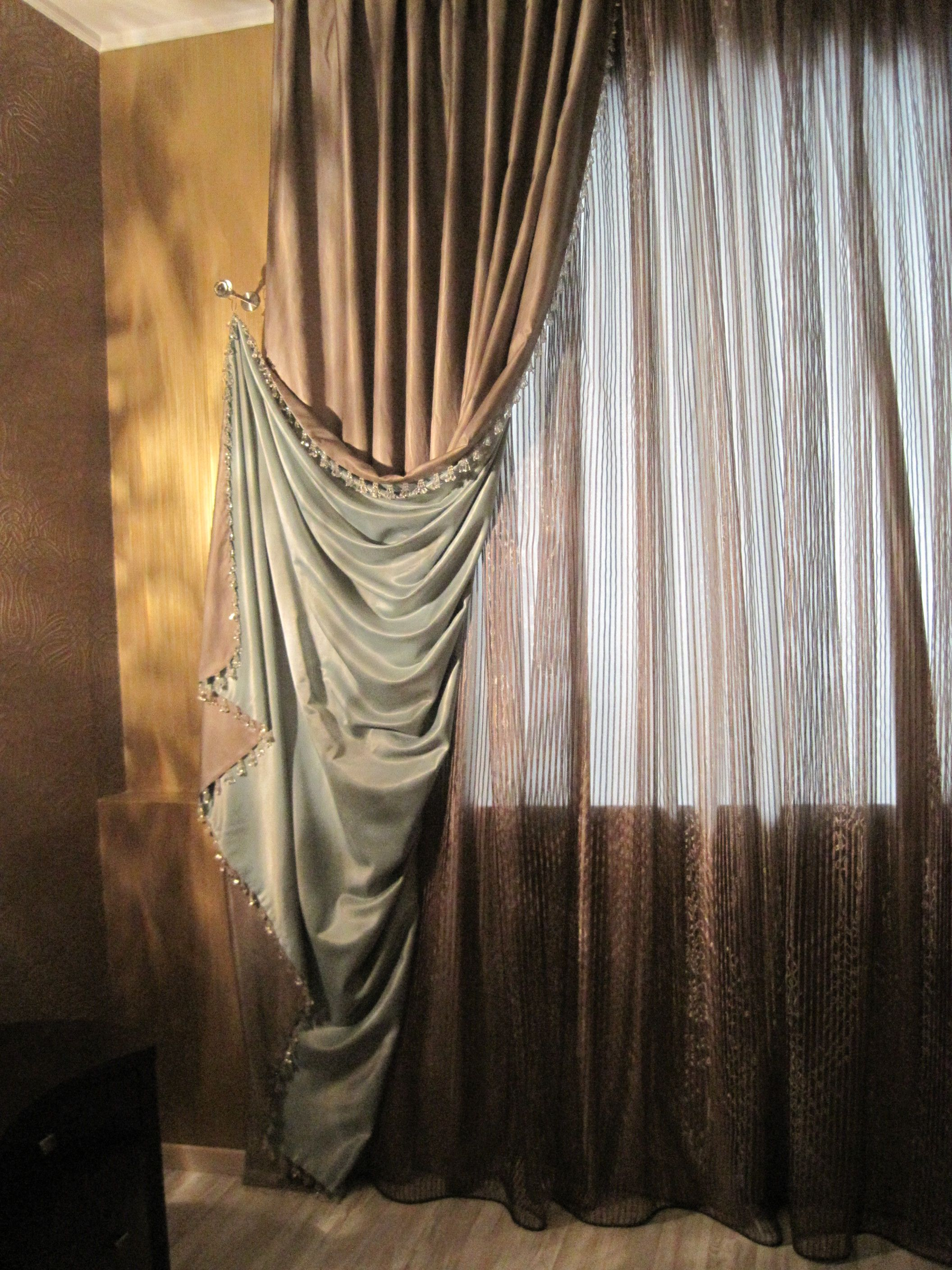 A dramatic pulled back drape contrast lined and complimented with a copper sheer delightful