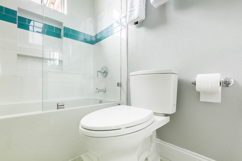 A hallway bathroom with double sink vanity . porcelain wood floor on ...