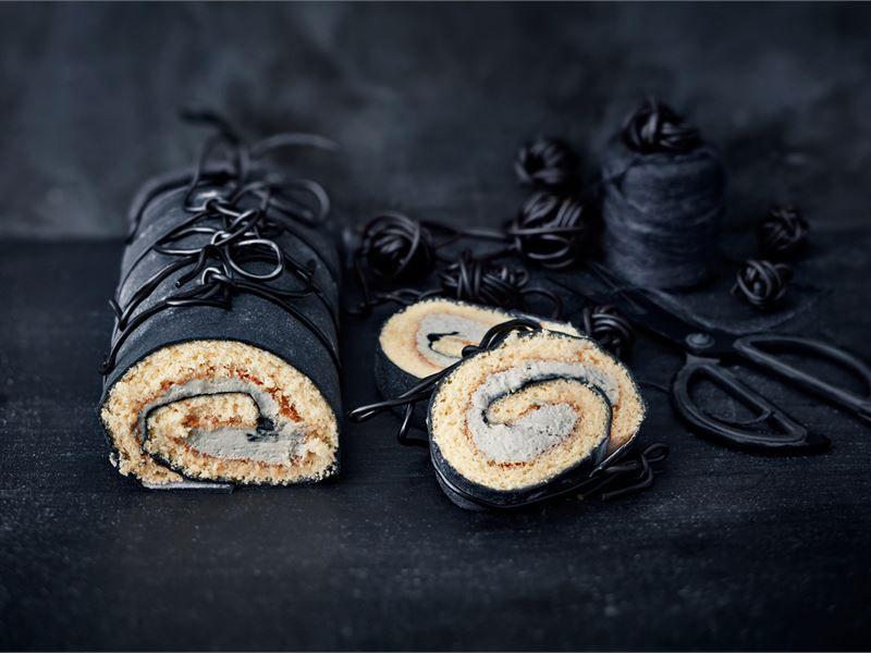 Näyttävän näköinen musta kääretorttu lakritsinauhoin koristeltuna on vaikuttava näky juhlapöydässä. Sitruunaisen kääretortun täytteessä maistuu myös lakritsi.