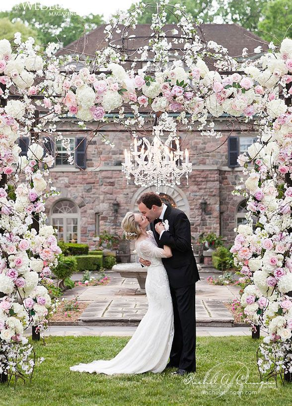 This show-stopping arbor overflowing with roses, hydrangeas and peonies is accented with a hanging crystal chandelier. #WeddingCeremony