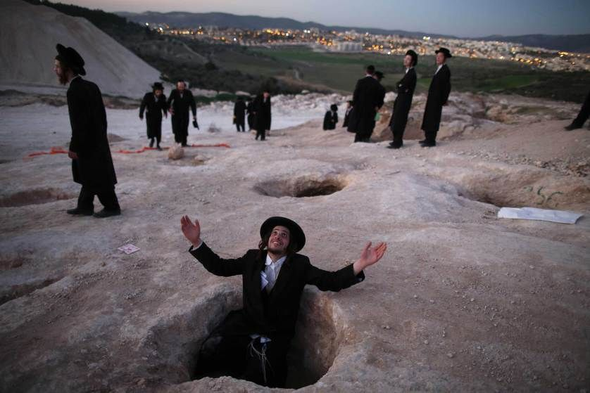 An Ultra-Orthodox Jewish man sits in a hole and prays during a demonstration in Beit Shemesh, Israel, protesting against the construction of new housing units that he believes would be built at the site of ancient Jewish graves, Feb. 12, 2014.