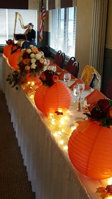 Head table with white lights, paper lanterns,  candles and fall colored rose centerpieces.  Anna Hagen, harpist playing in the background. Angela and Cory 10-17-15.