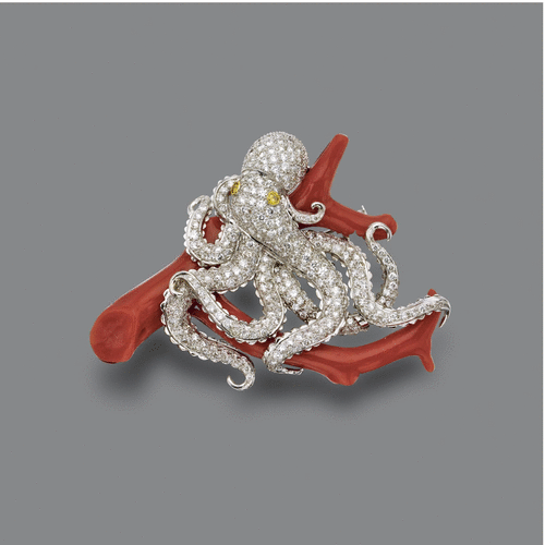 DIAMOND AND CORAL OCTOPUS BROOCH The octopus pavé-set with numerous round diamonds weighing approximately 6.50 carats, the eyes set with 2 round diamonds of yellow hue, coiled around a coral branch, mounted in 18 karat white gold.