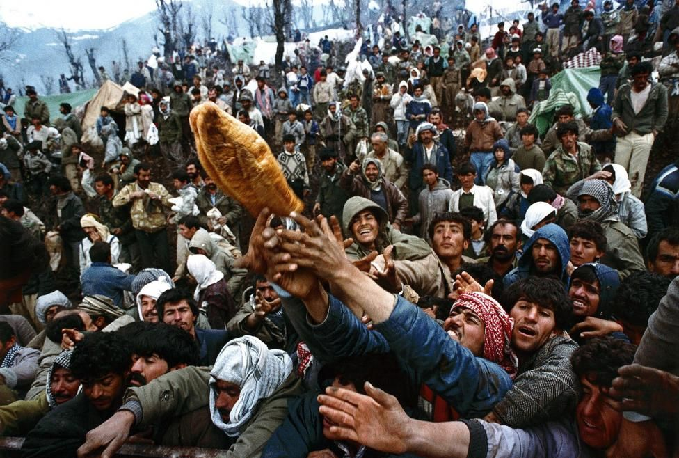 Frantic Kurdish refugees struggle for a loaf of bread during a humanitarian aid distribution at the Iraqi-Turkish border, April 5, 1992. Yannis Behrakis: At the end of the first Iraq war about 1.5 million Kurds were fleeing in panic trying to escape from forces loyal to Saddam Hussein. About 600,000 of them fled to Turkey but half of them were stranded in the mountains at the Iraqi-Turkish border. I hitch-hiked a ride on a...