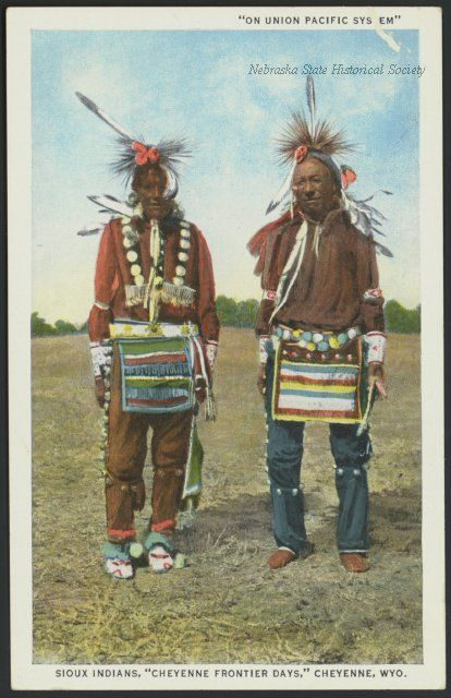This shows two unidentified Lakota Tribal members participating in the Cheyenne Frontier Days at Cheyenne, Wyoming. They are dressed in traditional ceremonial clothing, probably ready for a dance. This clothing includes feathers, beads, necklaces and headdresses. In the background can be seen trees. Date	circa 1905