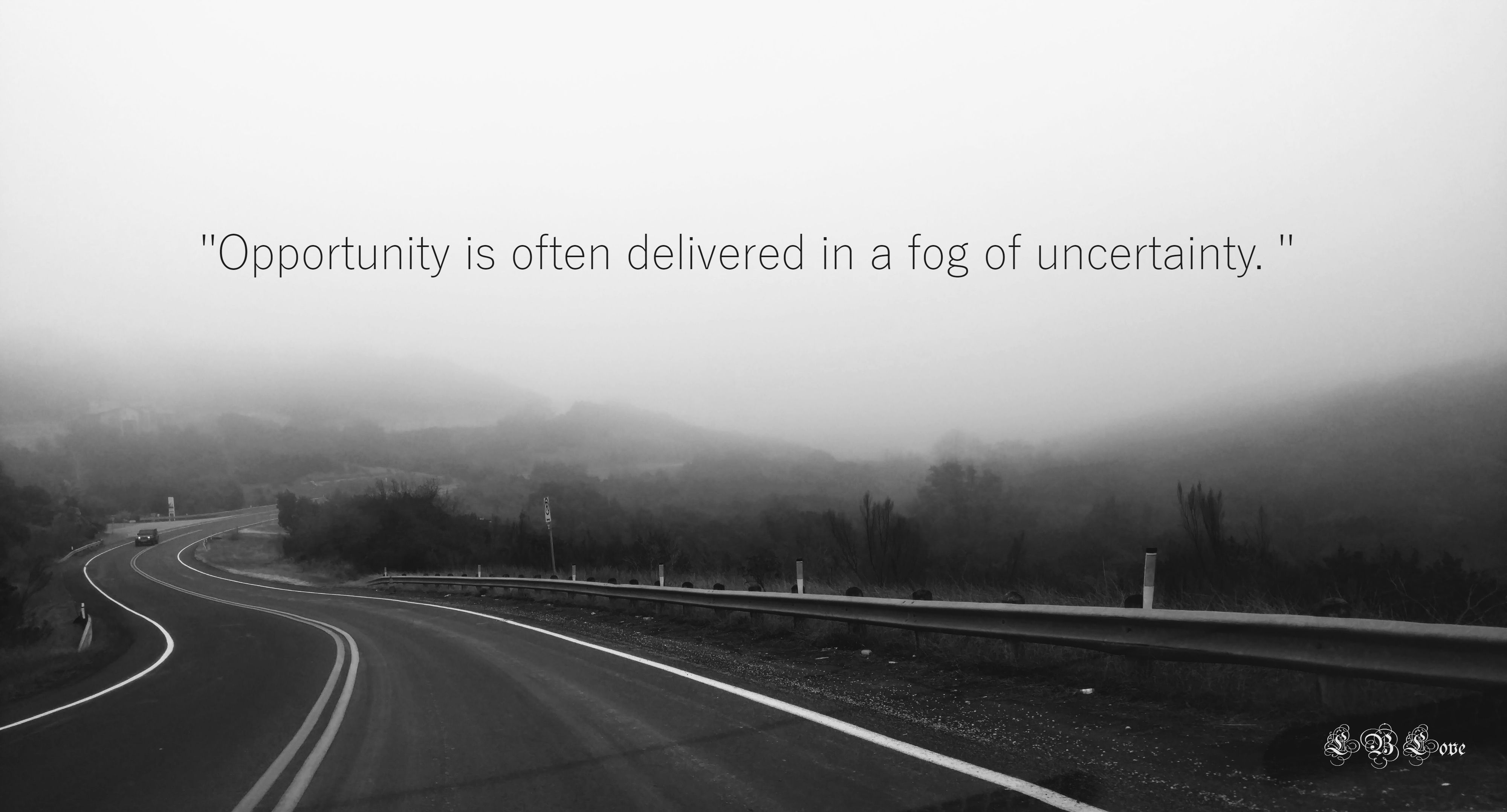 """Cloudy, foggy, windy road. Quote """"Opportunity is often delivered"""