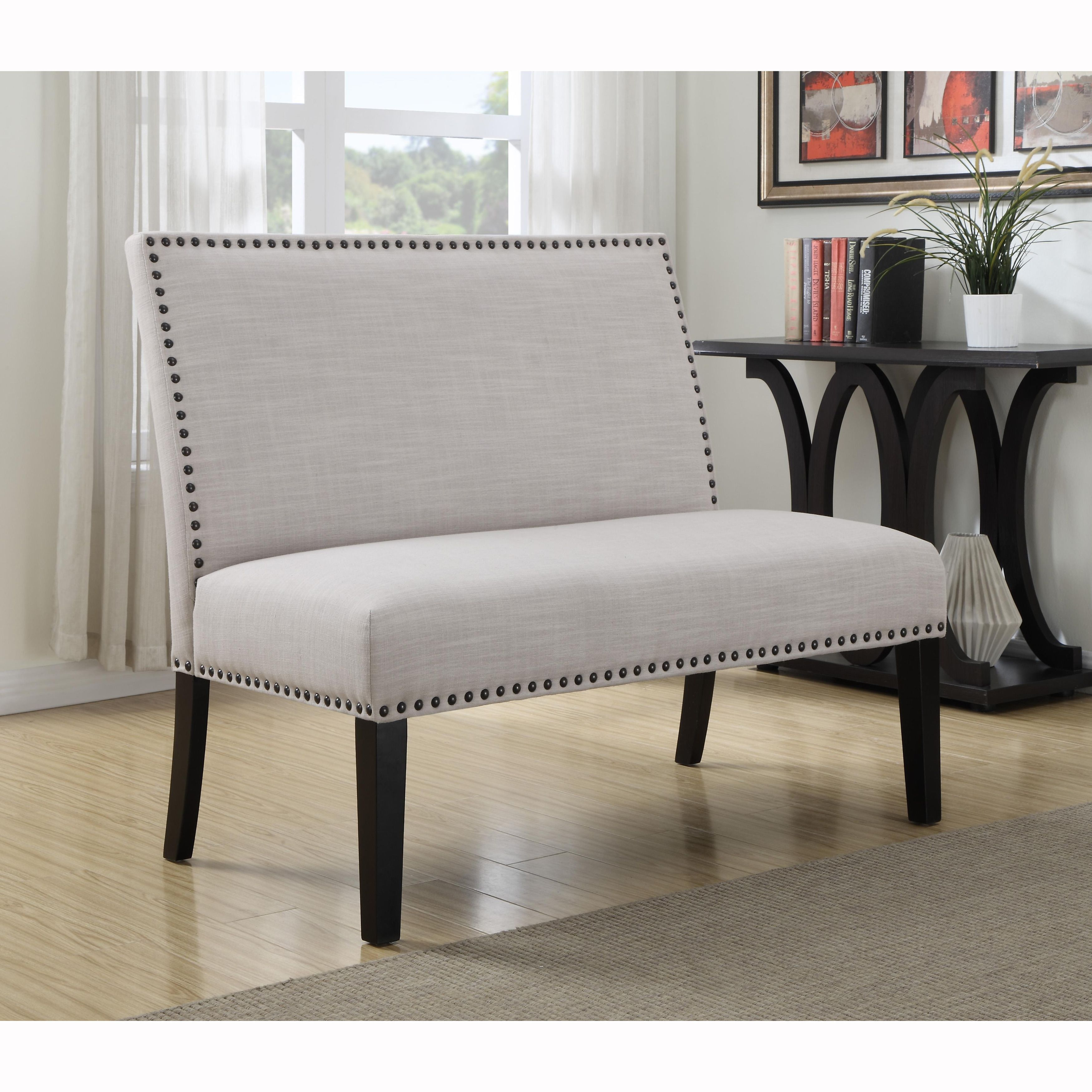 Cream upholstered banquette bench with nail head trim is for Banquette bench