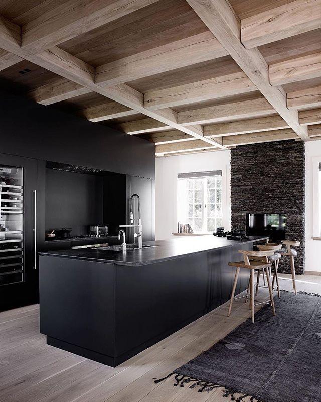 Black kitchen under a stunning oak ceiling