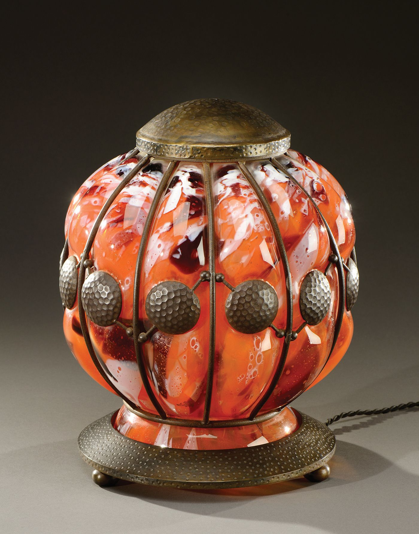 A rounded shape night light in orange coloured glass blown into a wrought iron netting. Signed «Daum Nancy». Circa 1920.