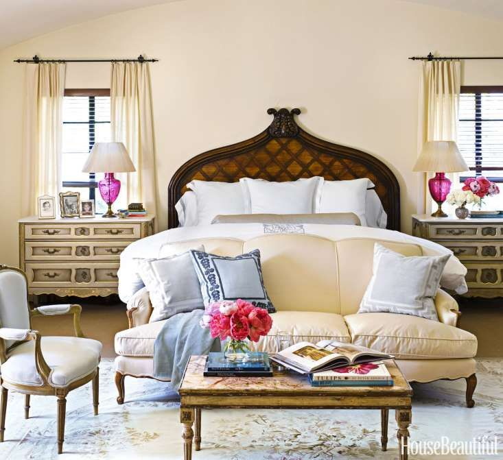 An 18th-century Italian carved-wood headboard is the focal point in the sun-filled master bedroom in... - Anne Schlechter