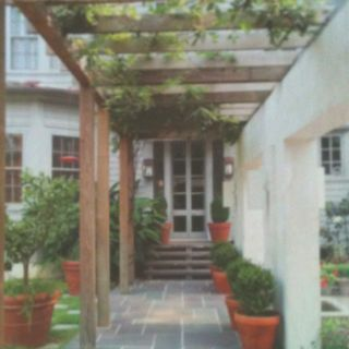 Vine covered arbor, stucco wall, slate tile, potted boxwoods...