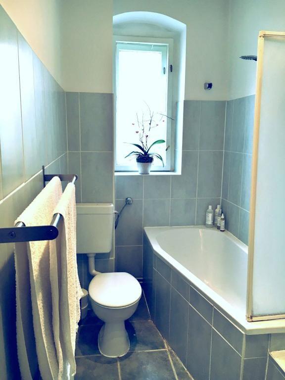 Badezimmer mit Fliesen in blau, Badewanne und dunklem Handtuchhalter ...