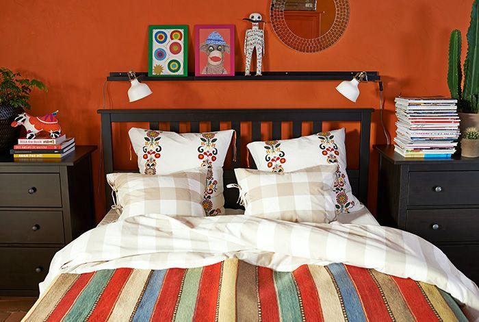 Sänky, jossa IKEA-lakanat. Kukalliset ja ruudulliset tyynyliinat, raidalliset lakanat ja monivärinen matto.