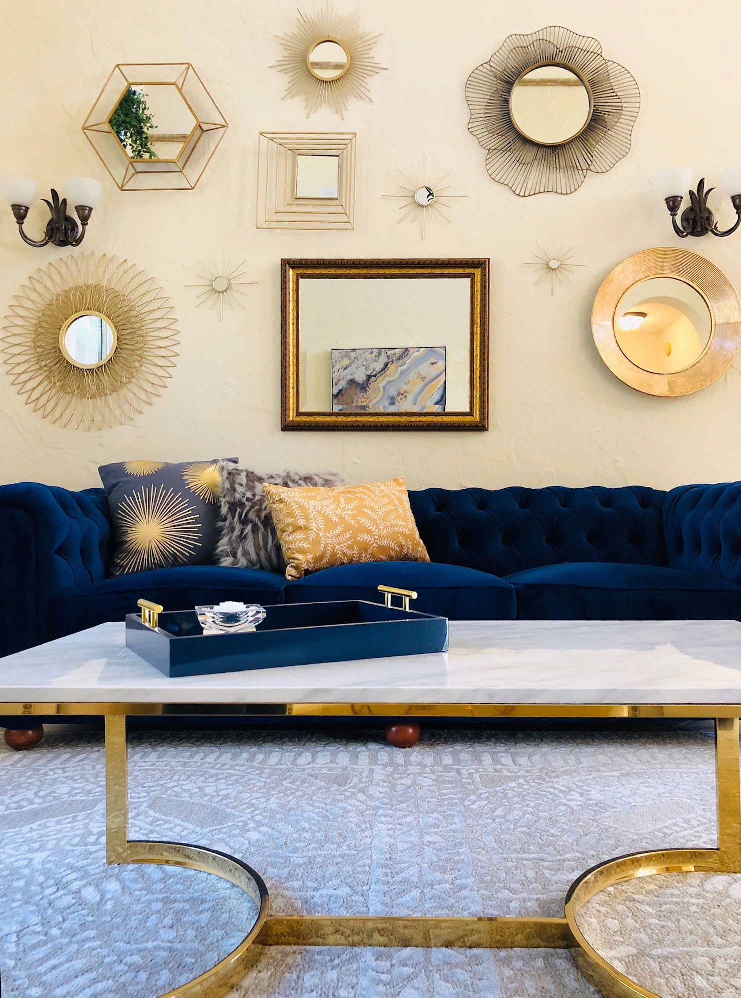 Classic Glam Living Room With Blue Velvet Chesterfield Sofa And Mirror Gallery Wall Geode Art And Marble Cof Glam Living Room Mirror Gallery Wall Living Room