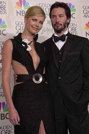Actress Charlize Theron and actor Keanu Reeves pose ...