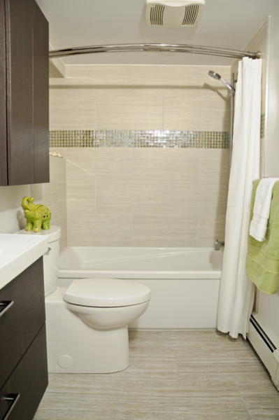small beige bathroom with curved shower curtain rod  striped tile  green  and white accents. 5 Steps to Make Your Small Shower Look Bigger Without Remodeling