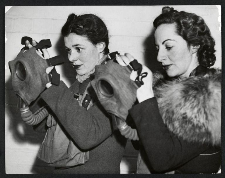 Anon. 'Two women donning gas masks as part of an air raid