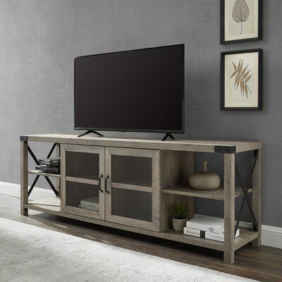 null Every family home needs a few pieces of furniture that are as functional and durable as they are handsome. Like this metal TV stand, for example: An industrial spin on traditional farmhouse style, this TV stand offers open and closed storage that's framed with exposed metal accents on the sides and top corners. Behind the tempered glass front, doors with soft-close hinges open to reveal adjustable shelves, while the side shelves are fixed and just right for displaying prized knickknacks or