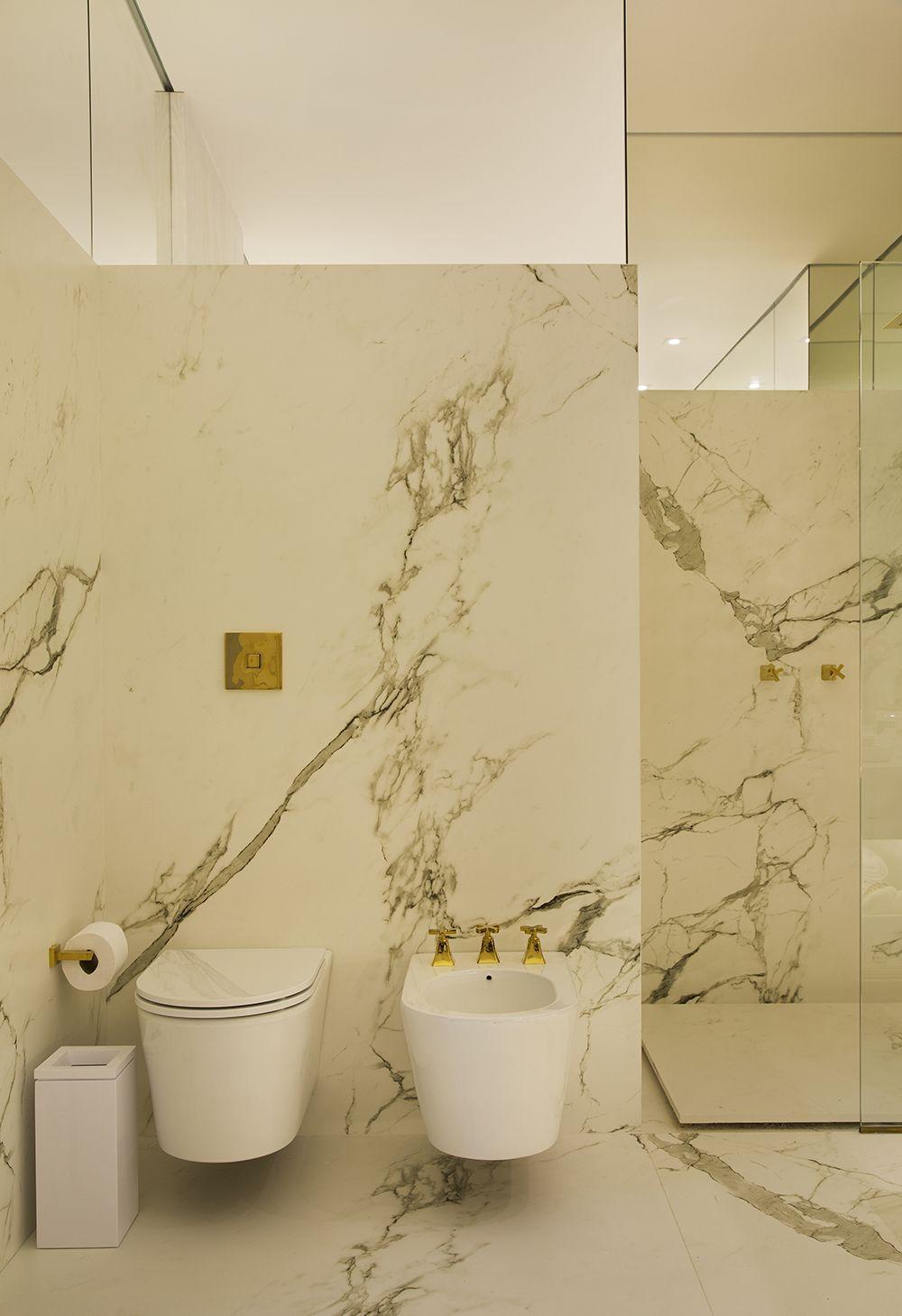 Banheiro com porcenalato paonazzetto, metais dourados e vaso linha ...