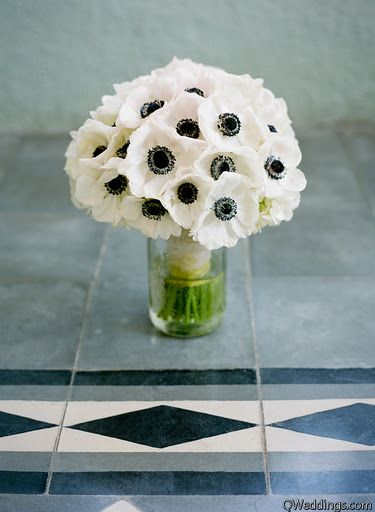 Pictured are white anemones with dark centers. These beautiful flowers are available for the most part year-round; however, there can be gaps in production where anemones are not available. Visit GrowersBox.com for more information on these stunning wedding flowers.