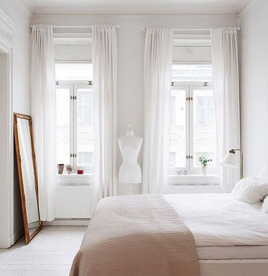 Simple Feminine Bedroom With High Ceilings And White Washed Floorboards
