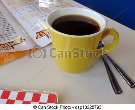 Reading the breakfast menu at the diner while enjoying a mug of coffee.