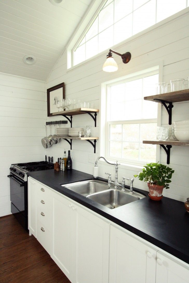 Over the sink shelf kitchen - Single Wall Sconce Light Fixture Some Floating Wood Shelves Black Kitchen Counter Double Stainless Steel Sink