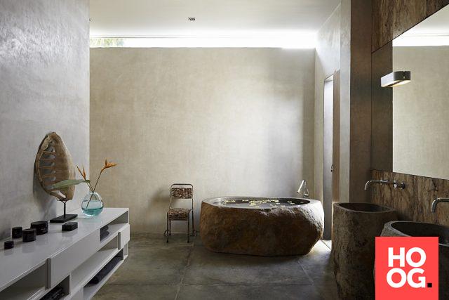 Badkamer in tropische stijl met ronde badkuip en dubbele wasbak