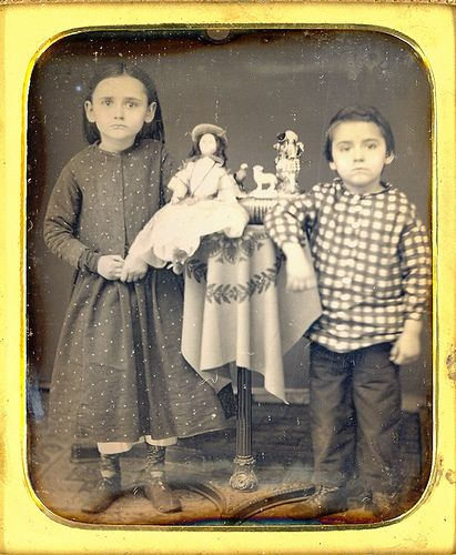 1/6 plate of two kids that look poor to me. It just might be that the doll is a studio prop and what is up with the Stafford shire figurines? Never the less an interesting photo. Notice how the little girl is holding her fingers and does not have her arm around the doll. The little boy looks mad at the world.