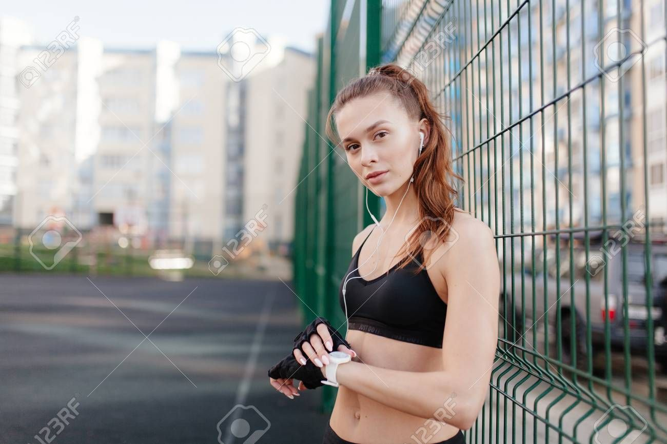 sporting a young girl in the gym and the stadium, warming up before exercise and listening to music ,