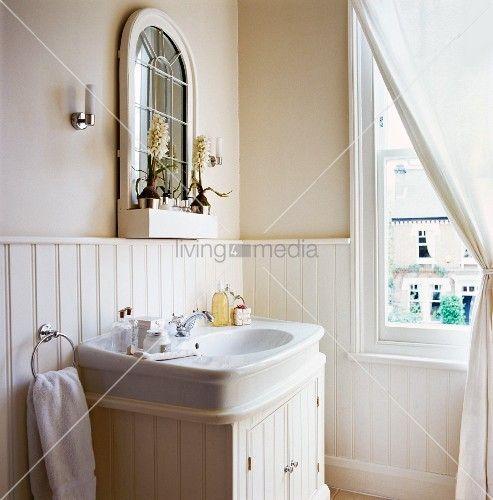 Spiegel auf weisser Holzvertäfelung über Waschbecken in elegantem ...