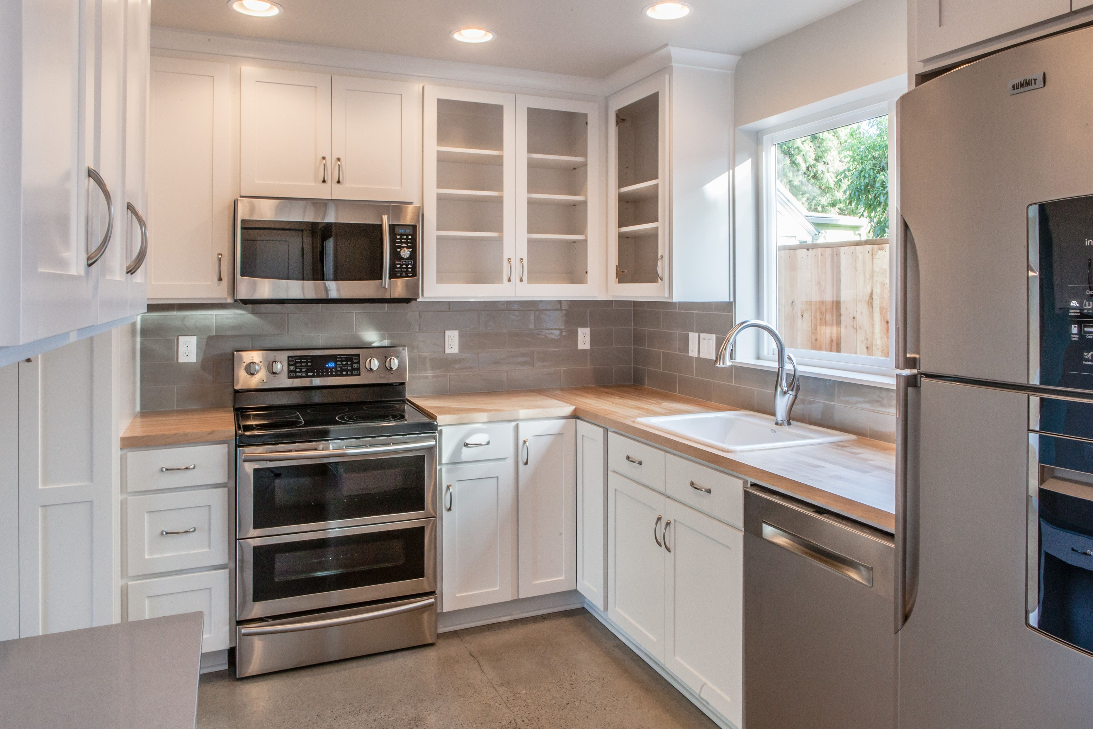 White Cabinets Butcher Block Counter Small Kitchen Stainless Steel Appliances Concrete Floor Michael Lindberg Kitchen Small Kitchen Butcher Block Counter