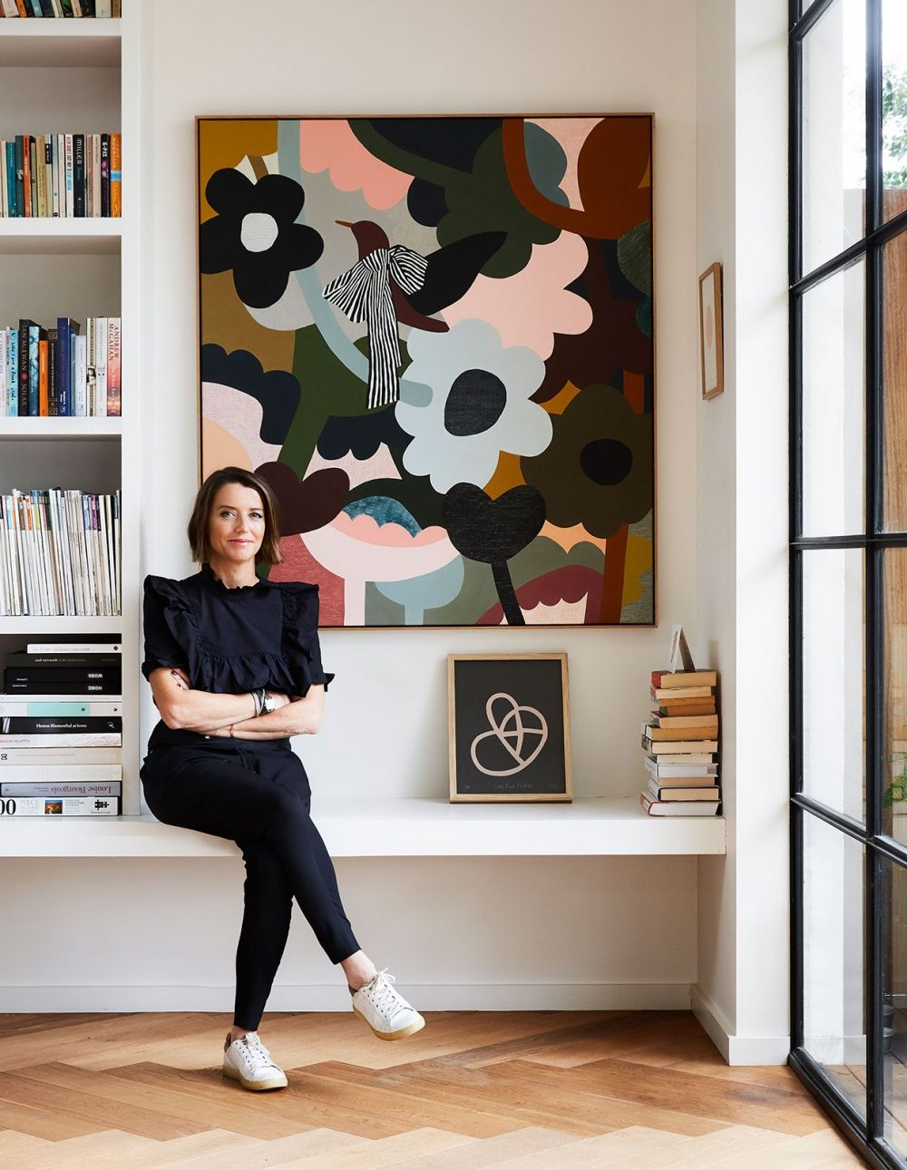 Rachel in front of her 'Peace Bird' artwork. 'We only have a couple of paintings in the house, normally on rotation based on what's sitting about the studio. This one will stay because it fits the nook so well!' Rachel tells us. Parquetry floors from Precision Flooring