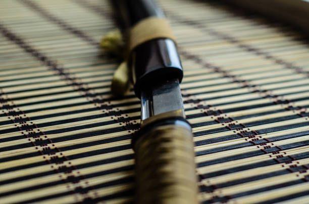 japanese sword katana on bamboo mat selective focus