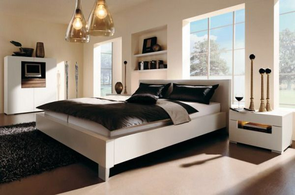 The black rug and bed spread, and white walls and bed make this a room with neutral colors.
