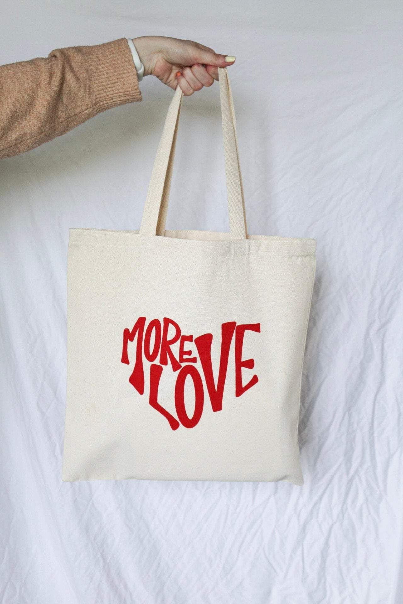 """**50% of proceeds from our 'More Love' products will go towards Be The Bridge and the Loveland Foundation. Founded by Rachel Cargle, the Loveland Foundation focuses on providing opportunities and healing to communities of color, especially women and girls. Be The Bridge is focused on bringing awareness and responding to the racial brokenness and systemic injustice within our country all while grounded in truth.** This adorable tote bag features a hand lettered quote reading """"more love."""" It's the"""