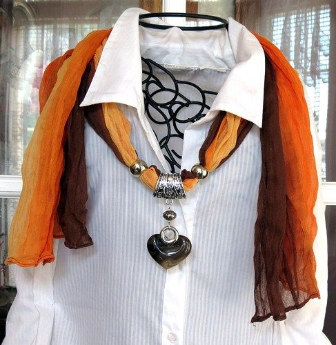 Multi colored scarf with acrylic heart pendant. Scarf is brown, orange, and gold with 3 silver plated sliders, 1 silver plated bead and an acrylic swirl heart pendant.