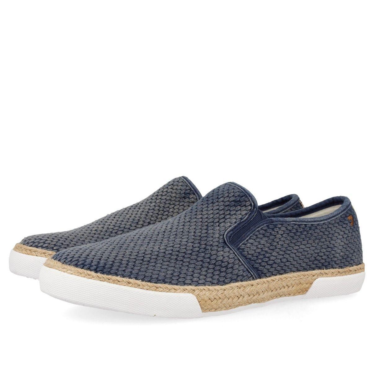 Zapatillas azules estilo slip on, con textura de piel de serpiente. Detalle de elásticos laterales para facilitar el calce y vivos en azul marino. Suela de yute natural trenzado y goma blanca. Corte en textil y forro y plantilla de tejido.