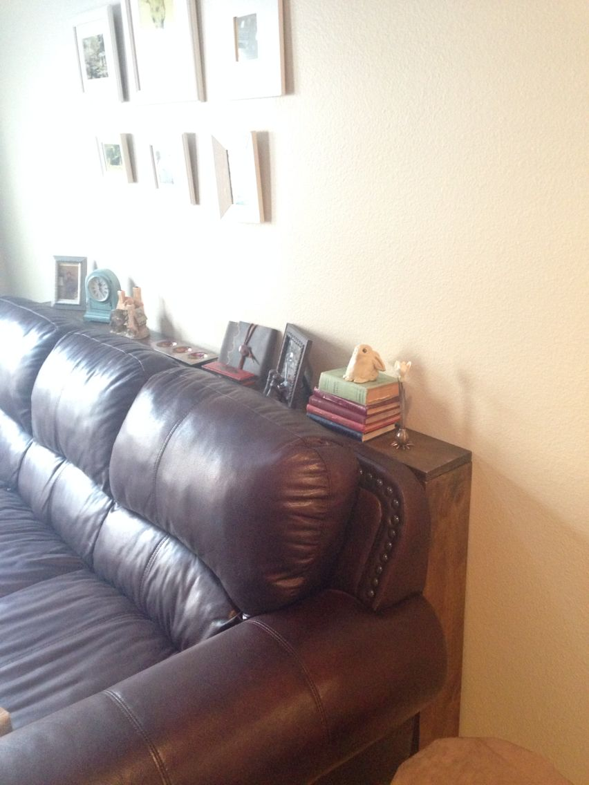 """DIY sofa table, 3 6"""" boards connected with L brackets and anchored to the wall"""