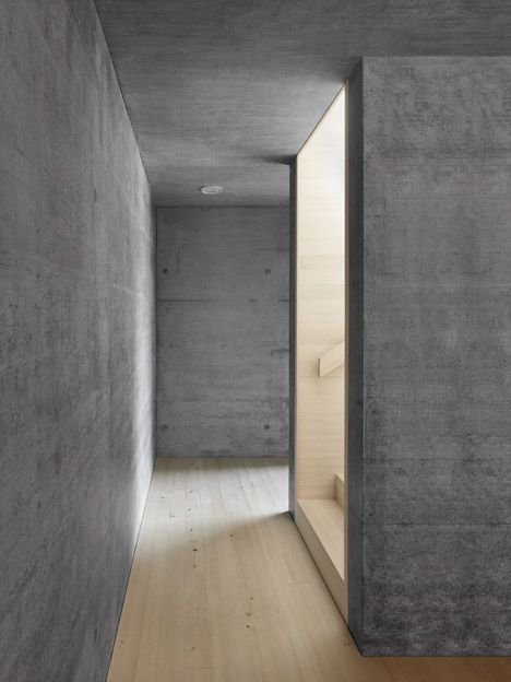 Wooden staircase inside a concrete corridor. Haus am Moor by Bernardo Bader Architects.