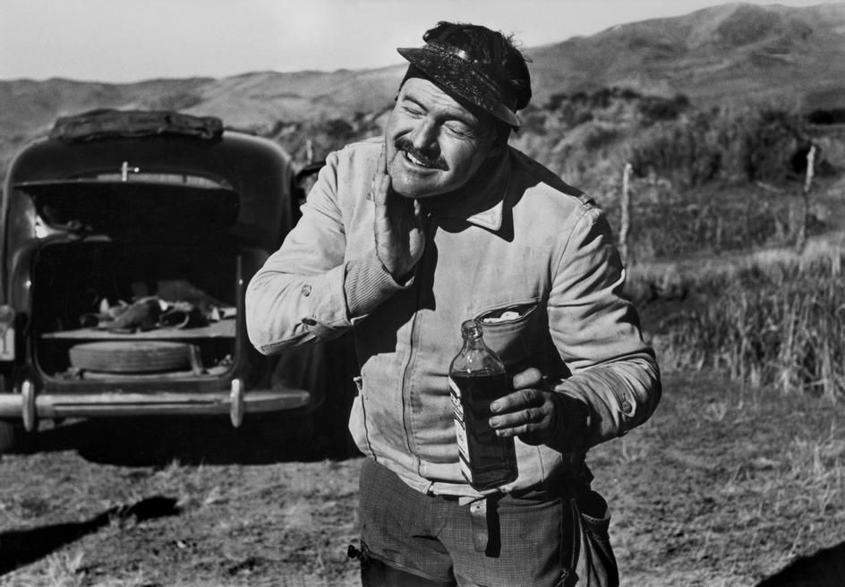 Idaho, USA. US writer, Ernest Hemingway, takes a break to freshen up during a hunting trip by Robert Capa, (1940)