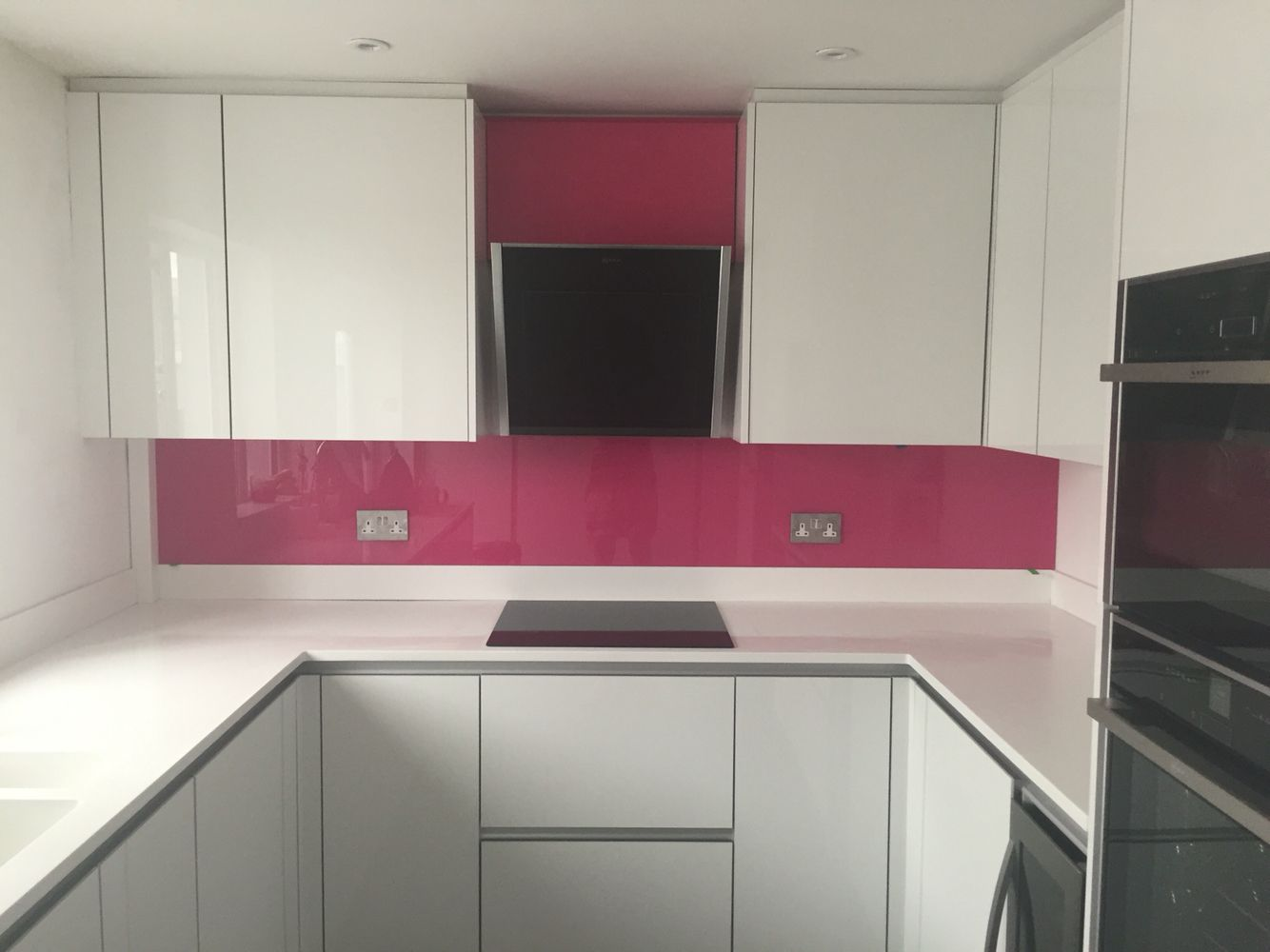 white kitchen with pink splashback