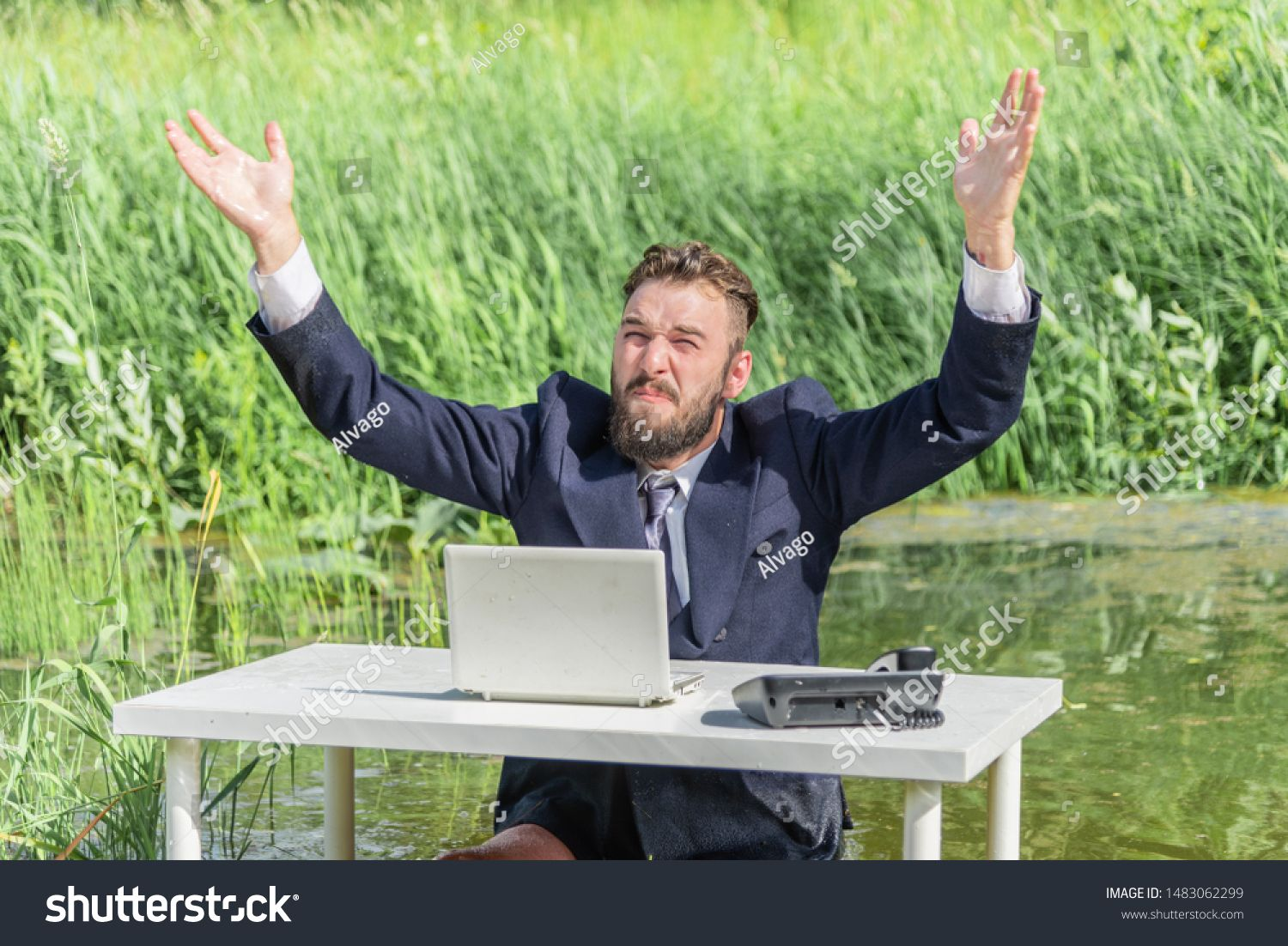 a man in a business suit sits at a table in a swamp with hands up concept of office employee and problems at work
