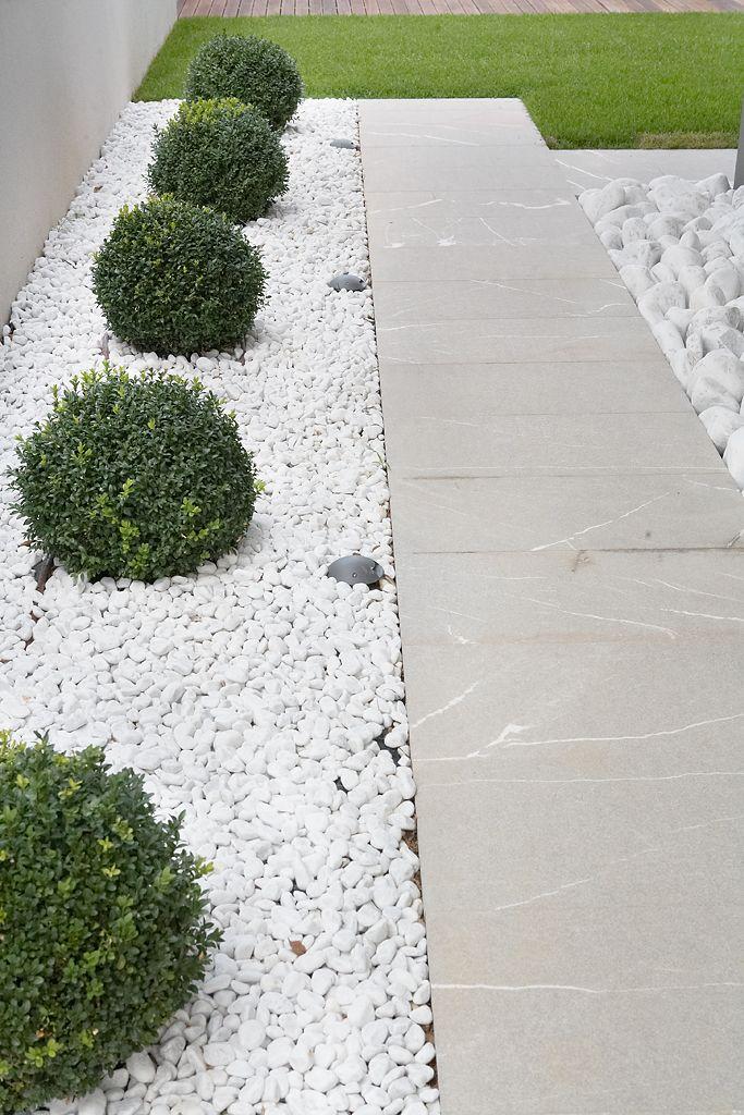 Blanda stengång med grus på framsidan. Plantera eventuellt några buxbom istället för buskarna vid garage väggen. Buxbomen är också vintergrön, tar mindre plats och dess form mjukar upp.