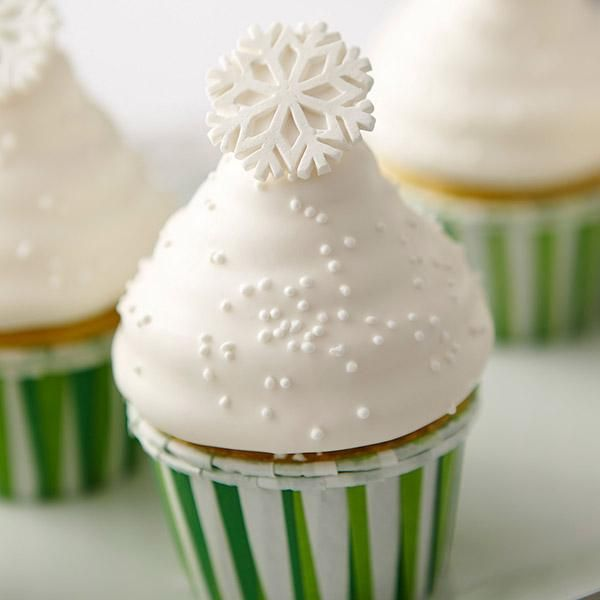 Christmas Candy-Dipped Cupcakes With Sparkling Snowflakes - Cause a flurry of excitement with these candy-dipped cupcakes. The secret is freezing the iced cupcake before dipping in melted Candy Melts candy.