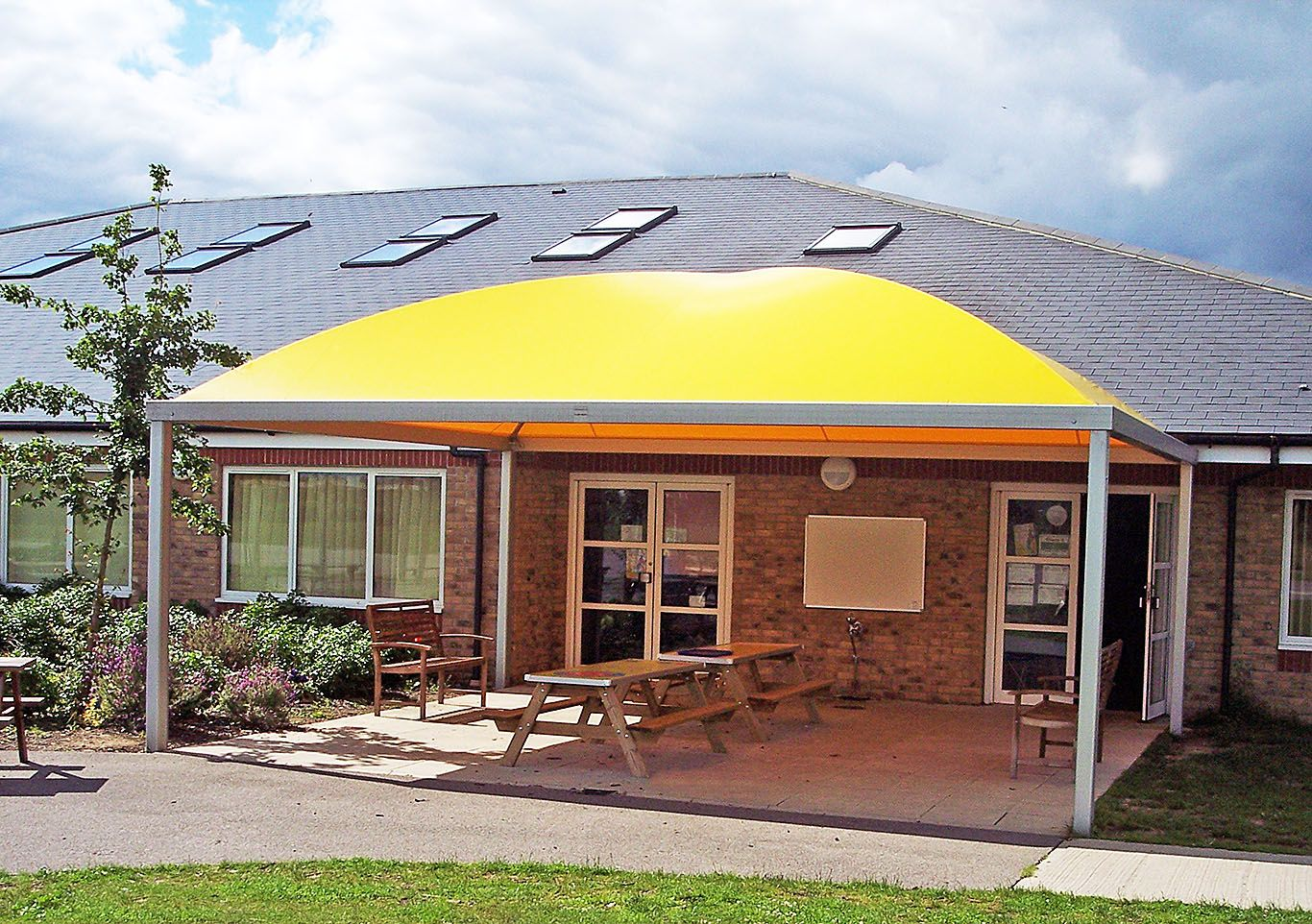 Yellow Cube canopy providing shade and shelter for a school's outdoor seating area.