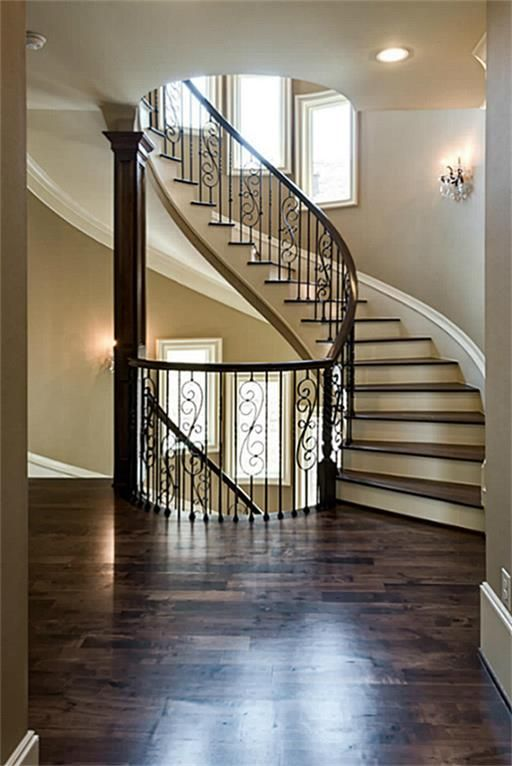 Stunning 3 Story Open Spiral Staircase With Rich Walnut Hardwoods And  Custom Scrolled Iron Balustrades.