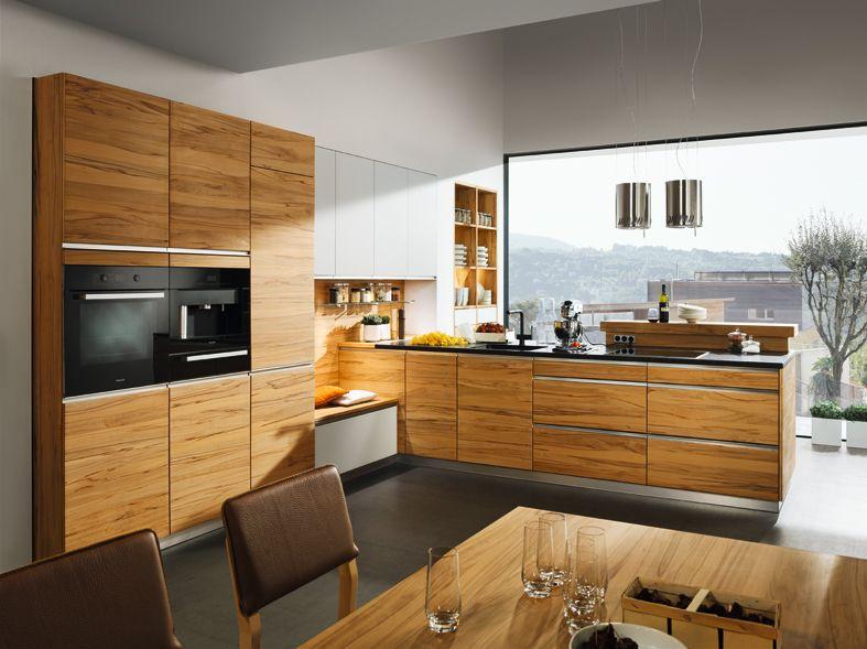 Massivholzküche aus donaueiche mit quer durchlaufender front naturstein arbeitsplatte hochschränke in gespachtelter rückwand eingelassen