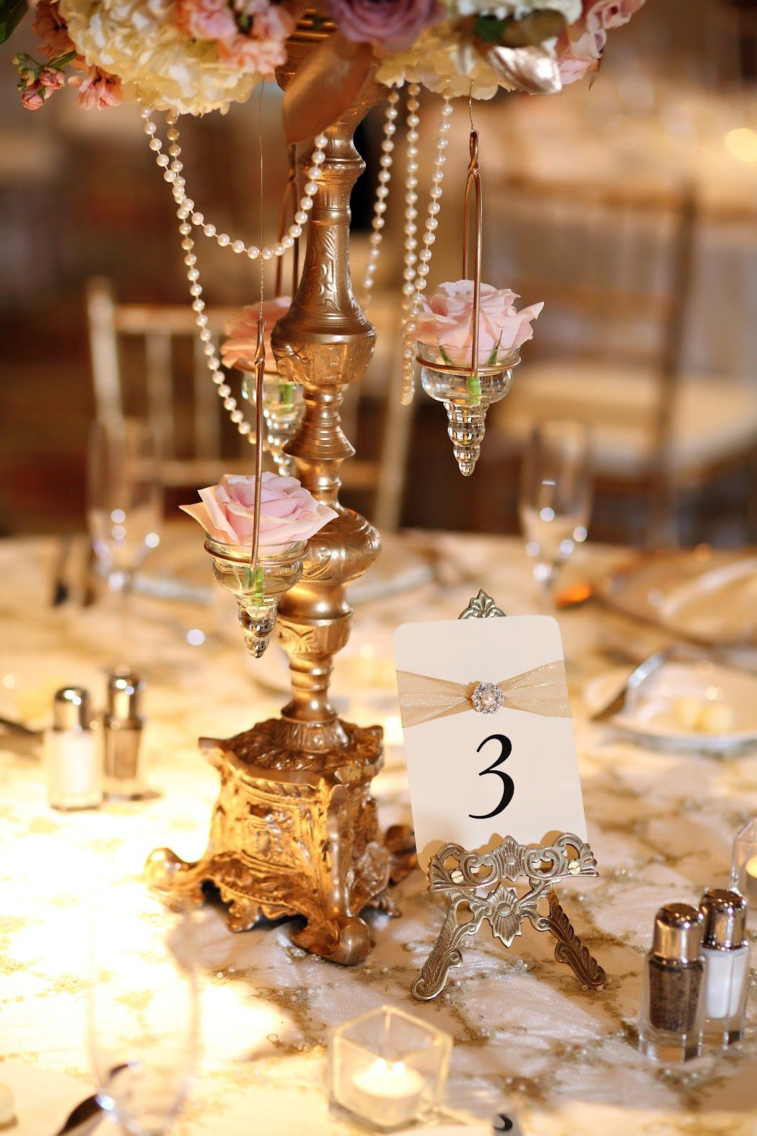 Gold Chandelier With Hanging Pink Rises And Pearls As A Centerpiece