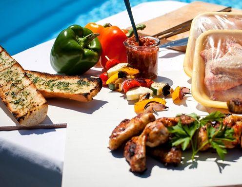 Hühnerkeulen und Hühnerflügerl im BBQ-Style mit Gemüsespieß und Knoblauchbaguette